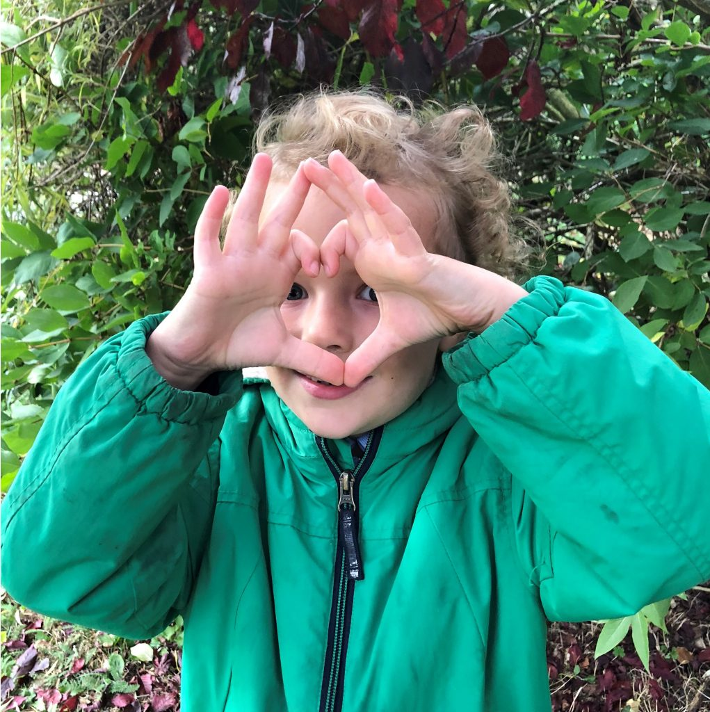 I love forest school boy with hands in the shape of heart